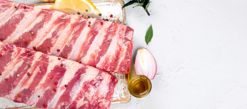 Fresh raw pork ribs seasoned with spices on light gray background