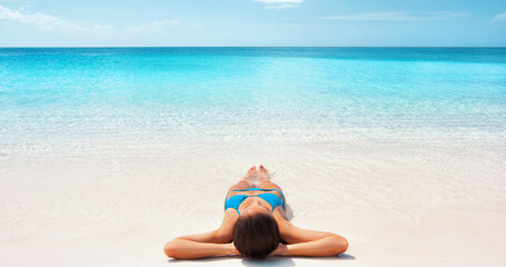 Paradise travel summer vacation Caribbean getaway bikini woman relaxing sunbathing on white sand beach in luxury resort with blue perfect water background.