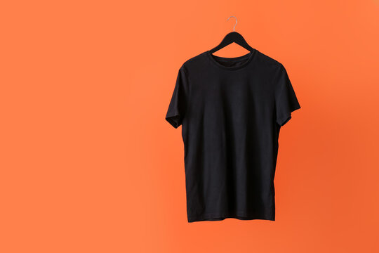 Hanger with t-shirt on color background