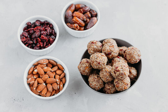Homemade energy balls made from dried fruits and oatmeal. Healthy food, snack. Vegetarian, vegan raw dessert. Energy balls and ingredients nearby on a gray background. View from above