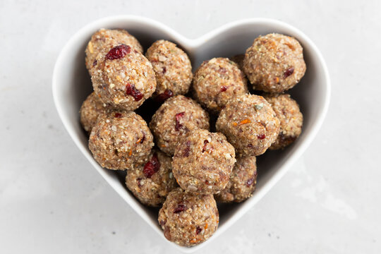 Homemade energy balls made from dried fruits and oatmeal. Healthy food, snack. Vegetarian, vegan raw dessert. Energy balls in a heart shaped bowl. top view