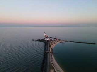Wall Murals Horses Paard van Marken, lighthouse at sun set along the water in the Netherlands, near Amsterdam in Marken. Aerial drone view.
