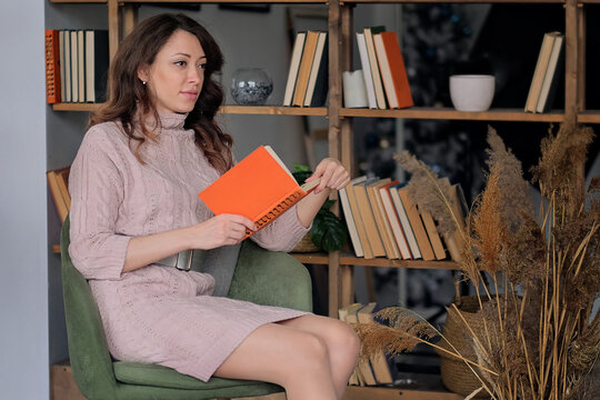 young modern woman in knitted dress reading a book in an armchair