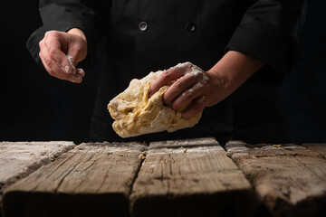 The dough in the hand of the chef on a dark black wood background. Baking bread, pizza, pasta. A recipe from the chef for pizza, bread or pastries. Home kitchen with space for text for menu design