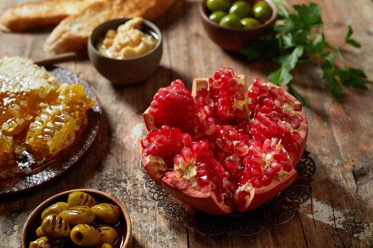 Halved pomegranate near olives and honey