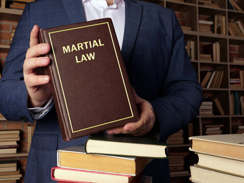 Attorney holds MARTIAL LAW book. Martial law is the temporary imposition of direct military control of normal civil functions or suspension of civil law by a government