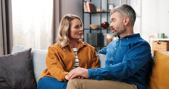 Portrait of cheerful happy Caucasian adult middle-aged couple wife and husband chatting having nice conversation while resting at home sitting on couch in positive mood, love family concept