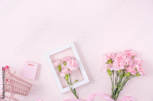 Concept of Mother's day holiday greeting with carnation bouquet on pink background