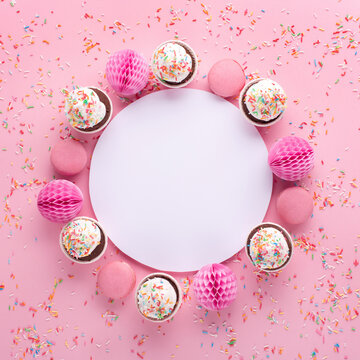 Empty white blank, gift box, paper decorations and cupcakes on pink sprinkles background.