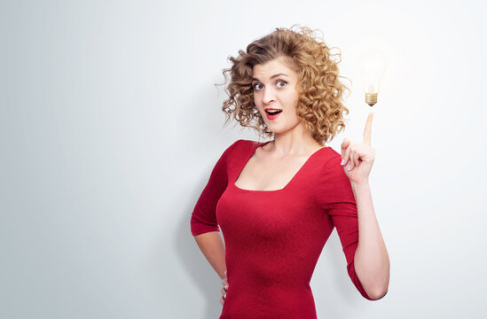 Young beautiful woman in red dress shows thumb up at a burning light bulb, making an successful idea gesture, on light background.