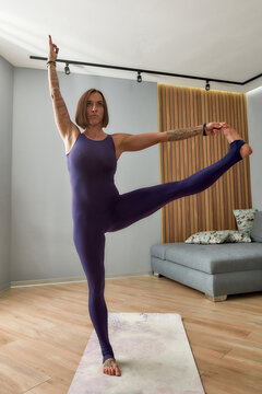 Full length shot of young woman in bodysuit working out, doing Extended hand to big toe yoga pose while standing in living room at home