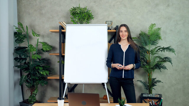 Positive woman teacher tutor standing near whiteboard listen teaches student remote video call chat. Smiling coach trainer looking camera records online business webinar master class in home office