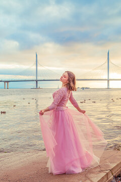 Young girl in a pink dress is dancing on the seashore.