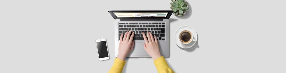 Fototapeta ノートパソコンをタイピングしている女性の手。卓上に置かれたスマートフォン、コーヒー、グリーン。真上から見たアングル。