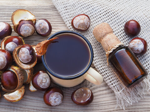 Ripe brown fruit of the aesculus hippocastanum tree and a drink in an enamel mug and a bottle on a wooden background, top view. Useful fruit of the horse chestnut plant for use in alternative medicine