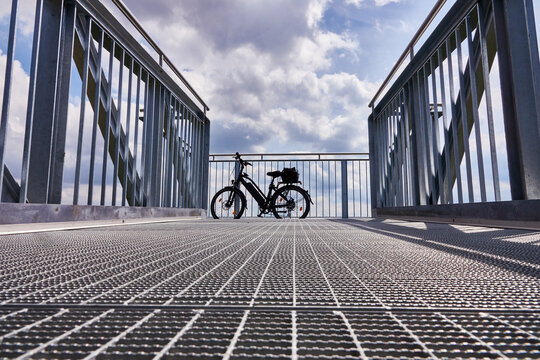 Bicycle leans against the front part of the railing of the viewing platform made of steel gratings