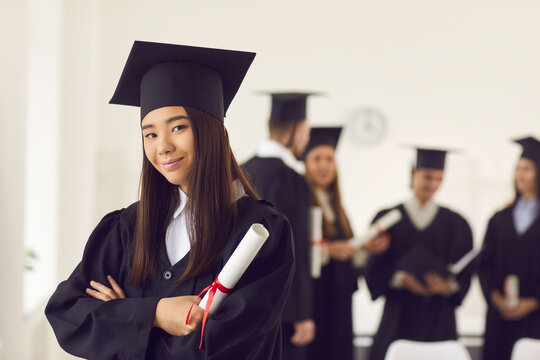 Portrait of a confident and proud Asian female student in a university graduate gown and with a diploma in her hands. Woman posing with crossed arms in classroom on the background of classmates.
