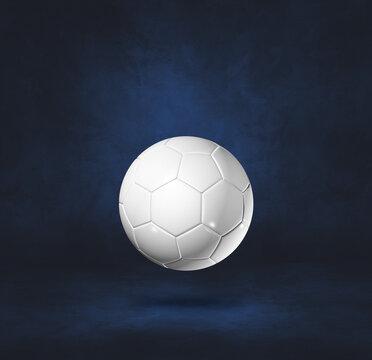 White soccer ball on a dark blue studio background
