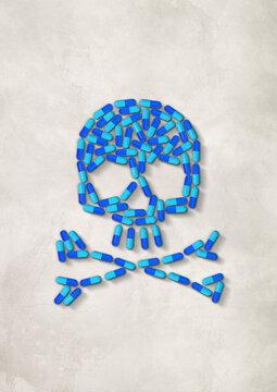 Skull made of blue capsule pills. White concrete background