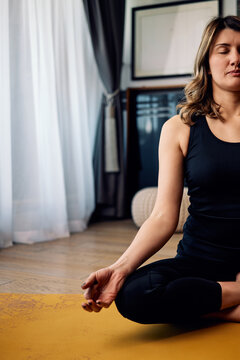 A middle aged woman sitting at home and meditating. Woman doing yoga at home