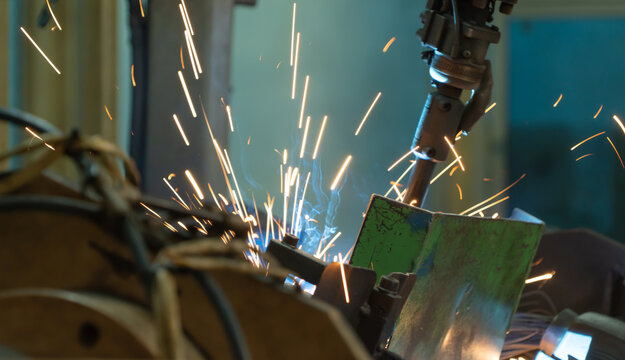 Steel smart robot welding hand system automated manufacturing machine engine in factory, industry metal supply chain technology production equipment in operation process warehouse. Welding sparks.