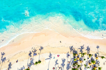 Beach vacation and travel background. Aerial drone view of beautiful atlantic tropical beach with straw umbrellas and palms. Bavaro beach, Punta Cana, Dominican Republic.