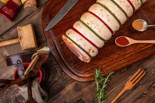 Pork belly rolled over wooden board and spices