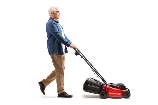Full length profile shot of a mature man mawing with a lawnmower machine