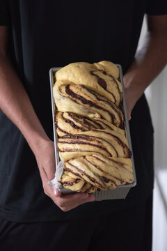 Vertical shot of a baker holding a raw dough of chocolate babka in a baking pan