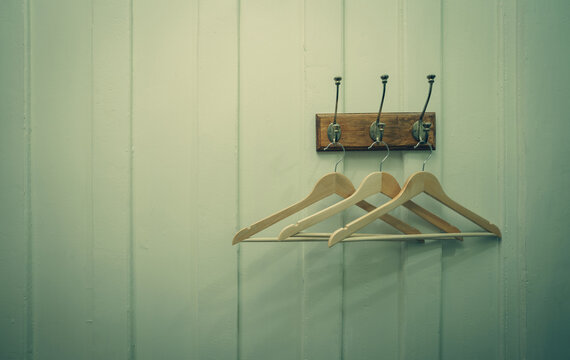 Brown wooden cloth hanger hanging on metal hook on white wooden wall background. Empty coat hanger in white vintage room. Hook install on wood wall with space for text. Rustic style fitting room.