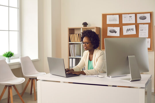 Experienced african american businesswoman typing on laptop making research for planning startup checking mail on netbook organizing working process. Female secretary at office desk with computer