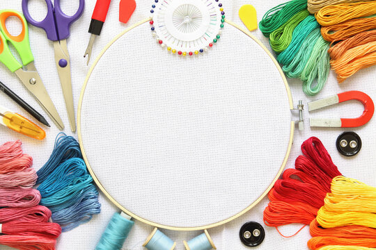 Sewing and embroidery kit with threads and needle, button, scissors and fabrics on frame