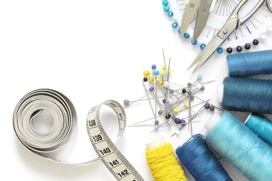 Sewing accessories template. Scissors, tape measure, spool of thread and needle on a white background.