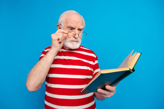 Portrait of attractive mad strict grey-haired man reading book science isolated over bright blue color background