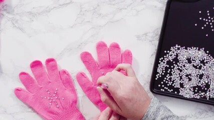 Wall Mural - Flat lay. Rhinestone pink kids gloves with snowflake shapes.
