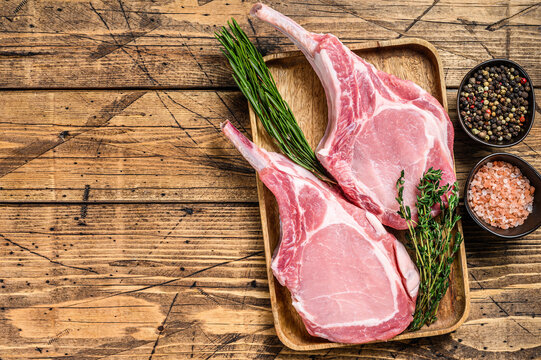 Fresh raw pork loin chops with pepper and salt. wooden background. Top view. Copy space