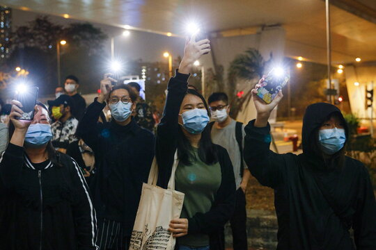 Supporters of pro-democracy activists hold flashlights as they wait for four of them to leave the West Kowloon Magistrates' Courts, in Hong Kong