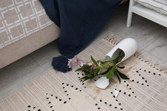 Broken vase and bouquet on floor in room
