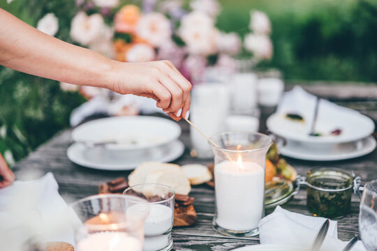 women ignite fire to decorative candles in stylish glass holders with thin wooden sticks at rustic table with elegant setting in garden closeup.