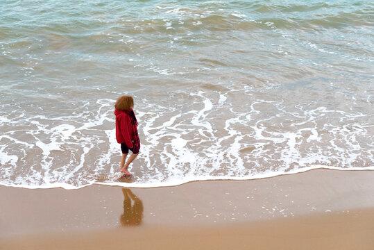 Femme se promenant les pieds nus dans l'eau sur la plage en hiver