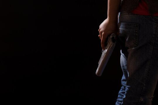 Juvenile delinquency. Child hiding gun. Criminal area.