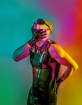 Multicolored creative artistic portrait of a rubber fetish, latex young man with fashion leather outfit on a colorful rainbow lighting and background.