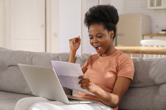 Excited millennial African American woman sitting on couch at home, holding and reading paper document, feel euphoric. Black girl receiving job, enjoy exam results or college admission letter.