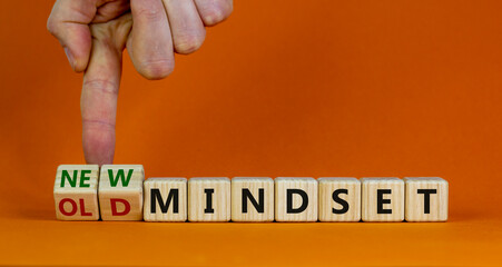 New vs old mindset symbol. Businessman turns the wooden cube and changes words 'old mindset' to 'new mindset'. Beautiful orange background. Business, new or old mindset concept. Copy space.