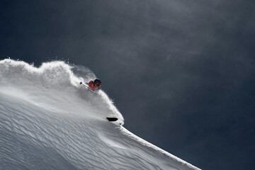 Male skier skiing down steep mountainside, Alpe-d'Huez, Rhone-Alpes, France