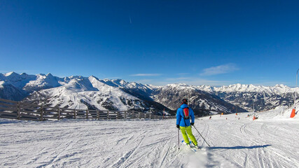 A man in colorful outfit skiing on the slopes of Katschberg in Austria. Panoramic view on the surrounding mountains. Winter wonderland. Sunny winter day. Perfectly groomed slopes. Happiness