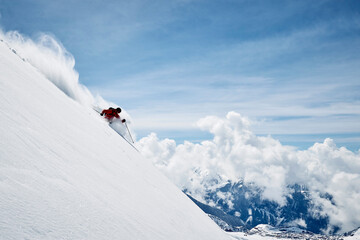 Landscape with male skier skiing down steep mountainside, Alpe-d'Huez, Rhone-Alpes, France