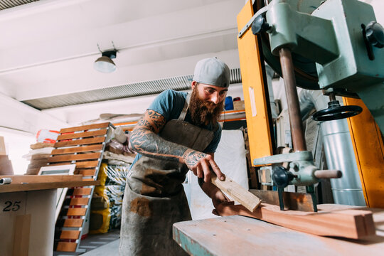 Axe maker cutting wood for axe handle in workshop