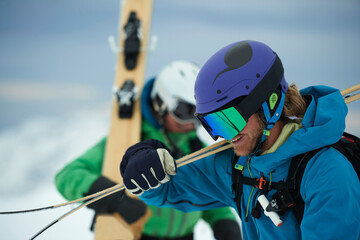 Two male skiers carrying skis in snow, Alpe-d'Huez, Rhone-Alpes, France