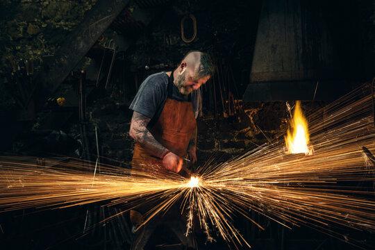 Mature male blacksmith making sparks hammering metal on anvil in workshop